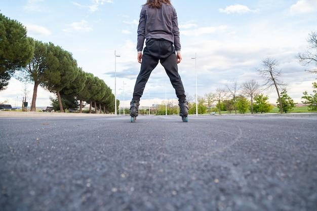 Cortar por baixo, vista traseira do jovem em sportswear patins na estrada no parque da cidade