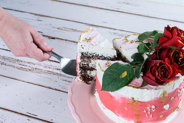 Cortar uma fatia de bolo de chocolate coberto com creme de manteiga de merengue suíço. três flores vermelhas no topo.