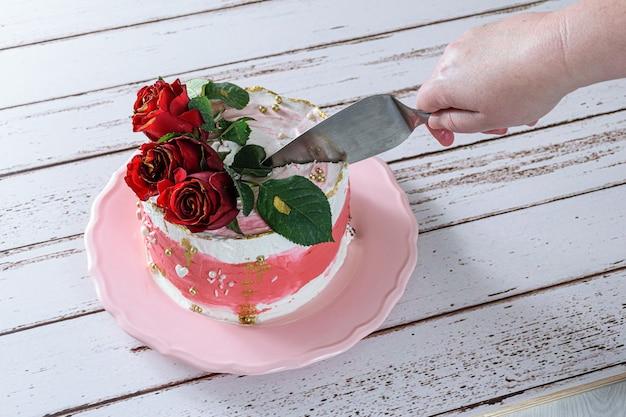 Cortar uma fatia de bolo de chocolate coberto com creme de manteiga de merengue suíço.