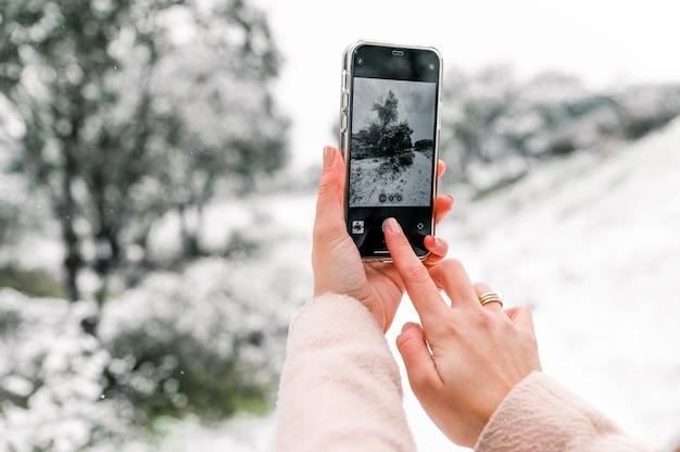 Cortar uma mulher anônima tirando uma foto de um bosque de inverno coberto de neve enquanto usa um smartphone