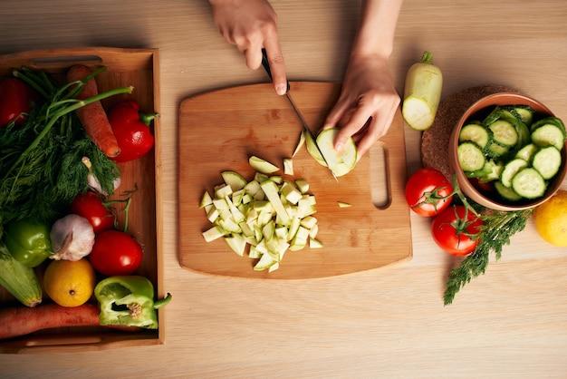 Cortar vegetais frescos em uma tábua de cortar vitaminas de frescor