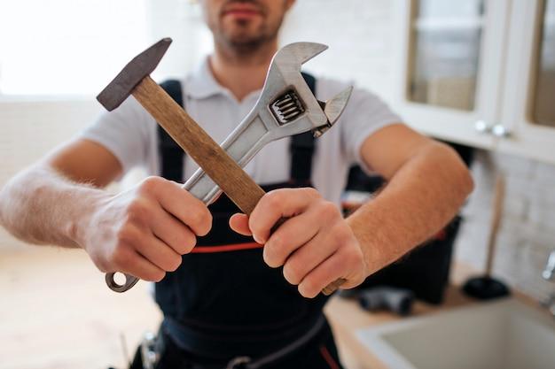 Cortar vista. encanador segurar chave e martelo cruzado. ele está na cozinha na pia. luz do dia.