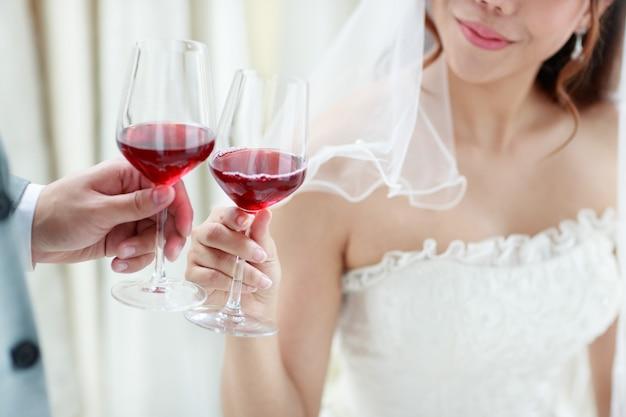 Corte a foto do noivo dando à noiva uma taça de vinho para a noiva em um vestido de renda branca no dia do casamento para comemorar com alegria. conceito de amor melhor dia