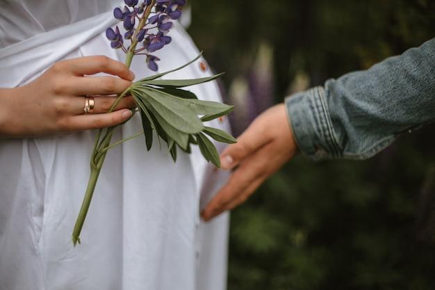 Corte a imagem da mulher grávida e a mão sensível segurando o tremoço violeta com a aliança de casamento e o homem tocando a barriga com uma criança