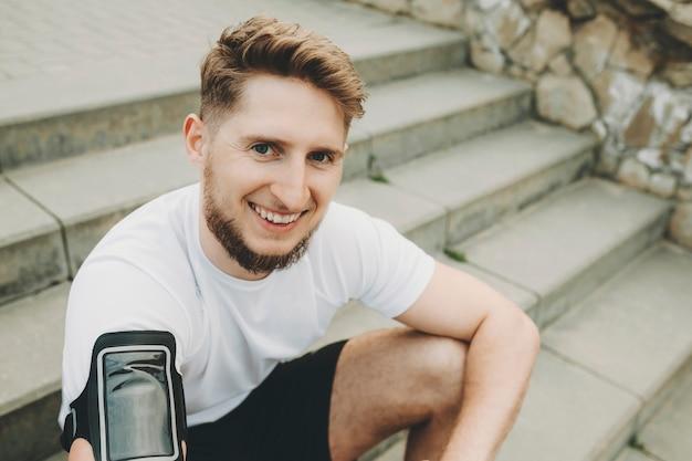 Corte a imagem de um homem feliz com a barba por fazer, de camisa branca e capa para smartphone no braço, descansando após o treino nas escadas de pedra e olhando para a câmera