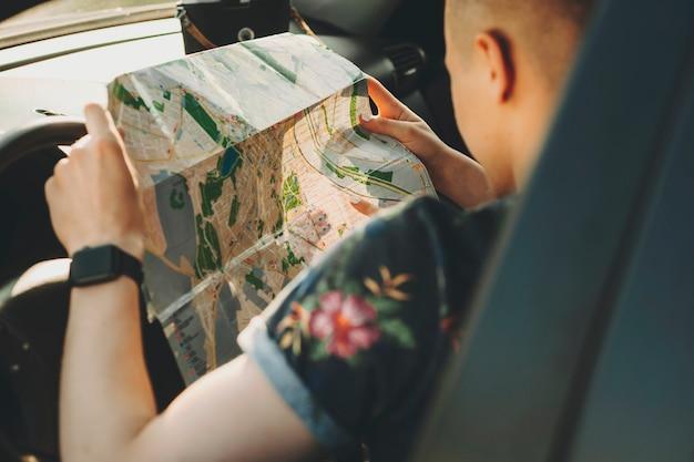 Corte a imagem traseira de um homem em uma camisa com estampa floral sentado ao volante e examinando de perto o mapa rodoviário nas mãos