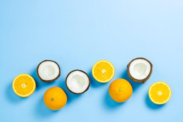 Corte a laranja e o coco numa superfície azul. vista plana leiga, superior.