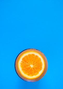 Corte a laranja na superfície do suco de laranja em um copo com fundo azul.