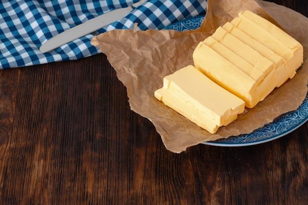 Corte a manteiga no prato com uma toalha azul na mesa da cozinha