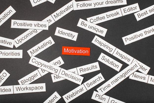 Corte a motivação de inscrição de papel em um fundo vermelho, cercado por outras inscrições em um fundo escuro. conceito de nuvem de palavras.