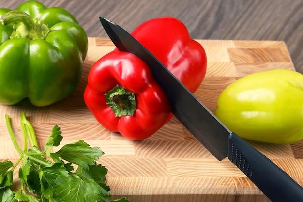 Corte a pimenta na tábua da cozinha. alimentos vitamínicos úteis