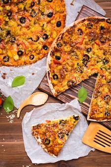 Corte a pizza com frango, tomate, queijo e azeitonas pretas. vista do topo