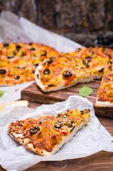 Corte a pizza com frango, tomate, queijo e azeitonas pretas
