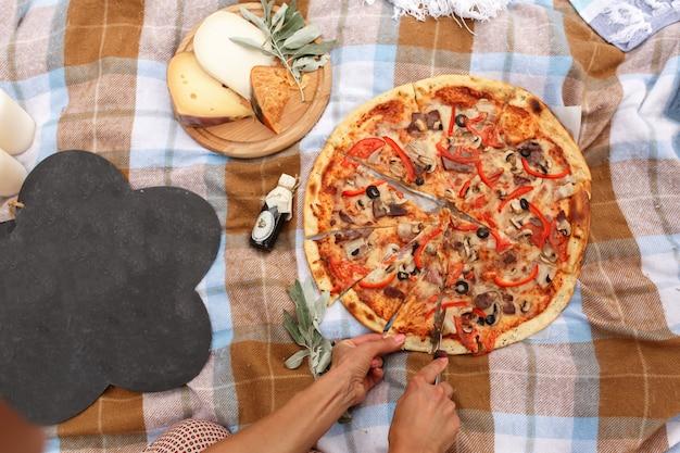 Corte a pizza no piquenique no parque de domingo.