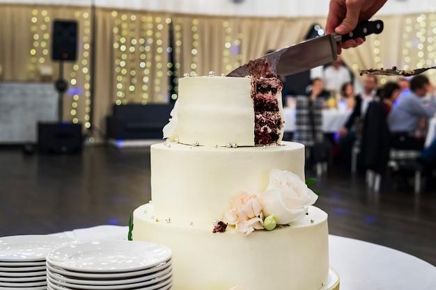 Corte a primeira camada de bolo de casamento de mástique branco no fundo do salão de banquetes. vista frontal da mesa com um lindo bolo de casamento e guarnições para servir os convidados. dividindo o bolo de casamento em partes.