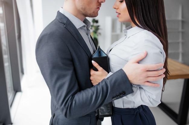 Corte a visão de jovem e mulher em pé muito perto um do outro. ele a abraçou.