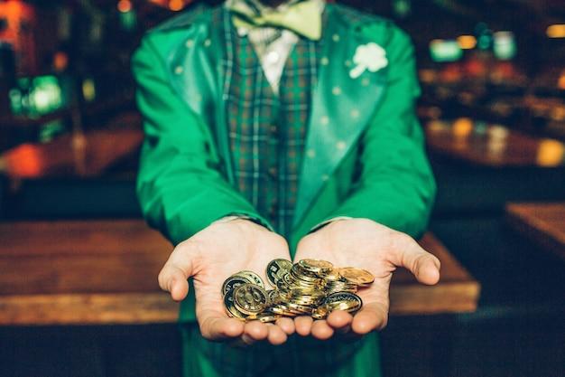 Corte a visão do cara em um terno verde, fique no bar e segure moedas de ouro nas mãos. ele os mostra para a câmera.