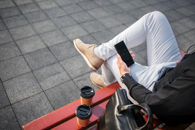 Corte a visão do homem de jeans, sentado no banco do lado de fora e segure o telefone preto. há duas xícaras e bolsa de couro.