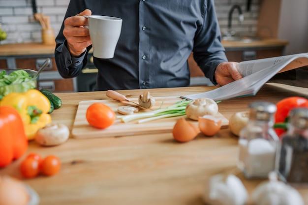 Corte a visão do homem sentado à mesa na cozinha. ele bebe de um copo branco e lê um diário. especiarias e legumes coloridos na mesa.