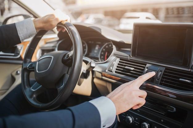Corte a visão do homem sentado no carro de luxo. ele segura uma mão no volante. outra mão toca nos indicadores no painel.