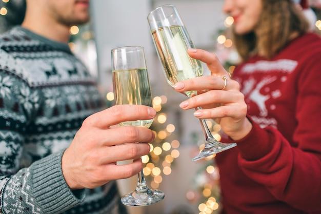 Corte a visão do jovem homem e mulher em pé na frente do outro. eles usam blusas de natal. casal tem copos de champanhe. ela sorri.