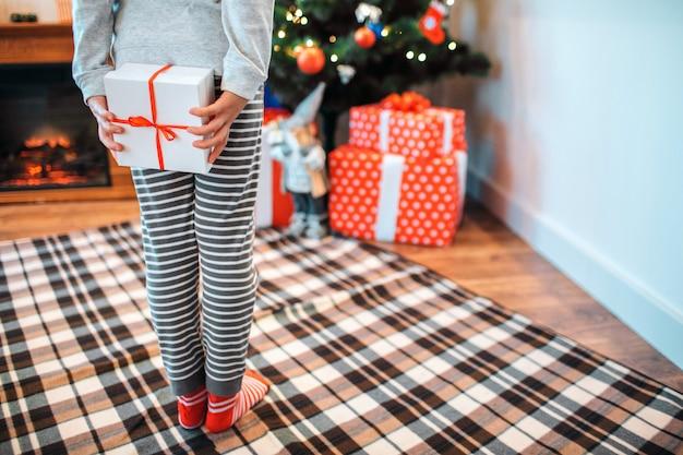 Corte a vista da pequena menina em pé de volta para a câmera. ela esconde uma caixa de presente branco. garota fica na frente da árvore de natal com presentes.