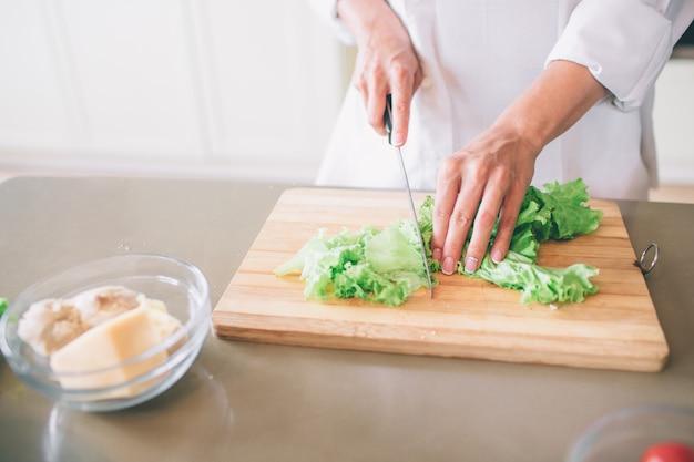 Corte a vista das mãos da menina, corte a alface na placa de madeira com faca. além disso, há uma tigela com frango e queijo cozido.