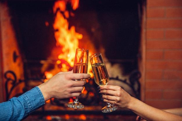 Corte a vista das mãos de homem e mulher segurando copos com champanhe. eles tocam na frente da lareira.