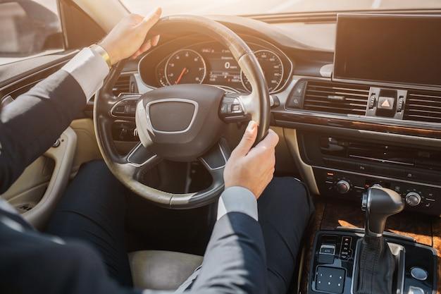 Corte a vista das mãos do homem de terno. cara senta-se no carro e mantém as mãos no volante. ele dirige.