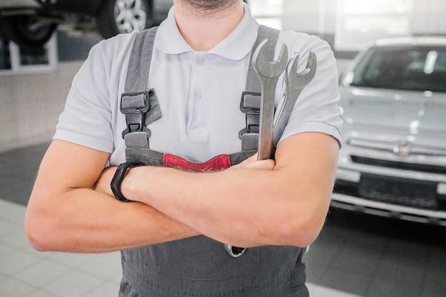Corte a vista das mãos do homem forte cruzadas. ele mostra músculos. cara usa uniforme cinza. carro branco está atrás dele.