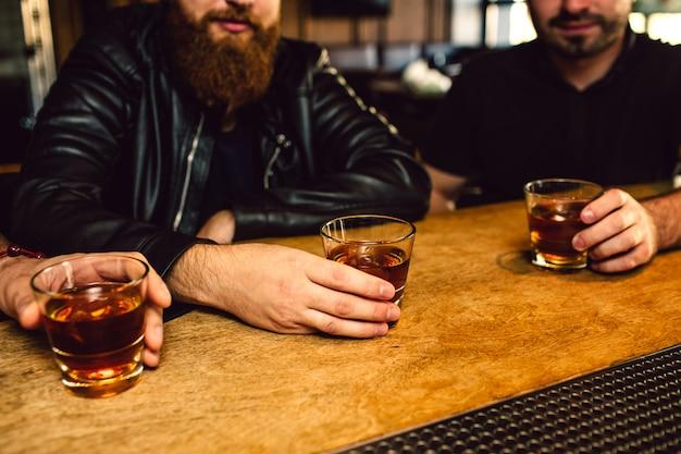 Corte a vista de três homens sentados no balcão de bar. eles seguram copos com rum. caras são sérios.
