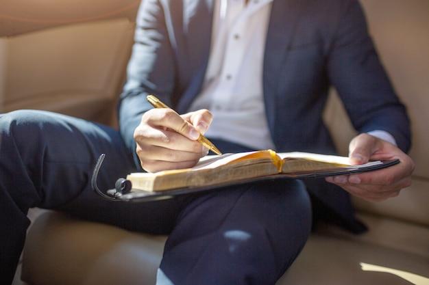 Corte a vista do corpo do homem de terno, sentado no carro de luxo e fazendo anotações no caderno.
