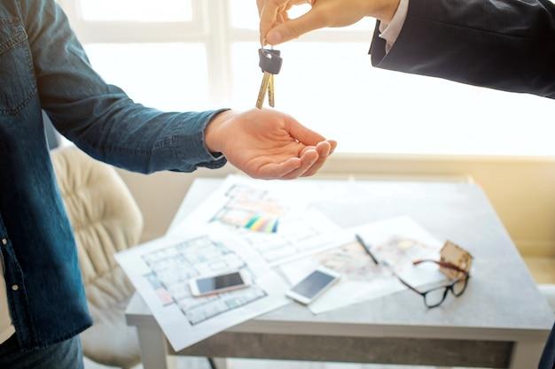 Corte a vista do homem que compra apartamento alugado. ele alcança a mão e pega as chaves do corretor de imóveis.