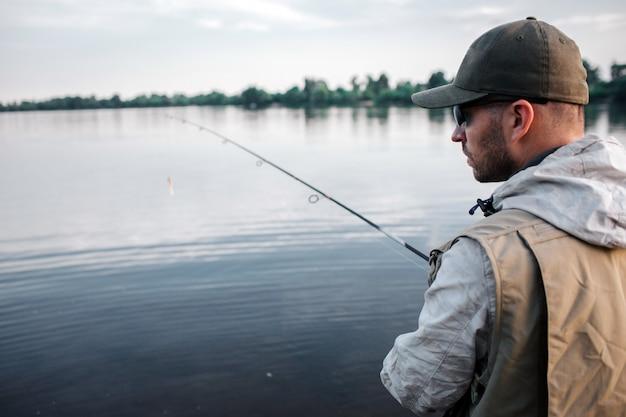 Corte a vista do pescador fica de costas para a câmera. ele está olhando para a direita. cara tem mosca nas mãos. está frio lá fora, então o homem veste suéter, colete e boné.