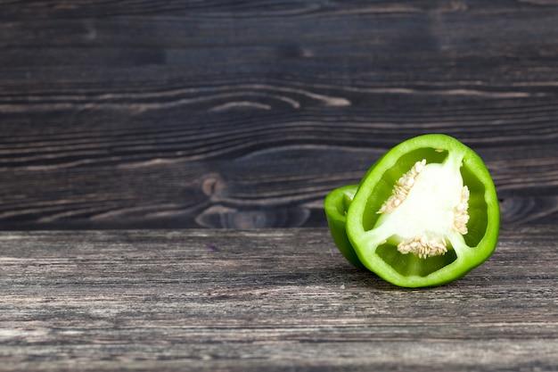 Corte ao meio um verde pimenta, close-up em um quadro preto com uma parede preta, área da cozinha