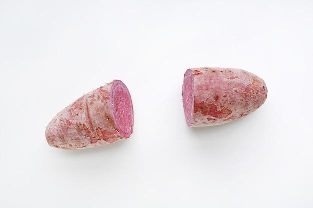 Corte as batatas doces roxas parcialmente no fundo branco.