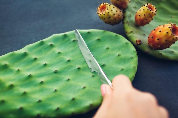 Corte as folhas de cacto com pera espinhosa ou fruta de cacto. comida saudável exótica em cinza. vista do topo