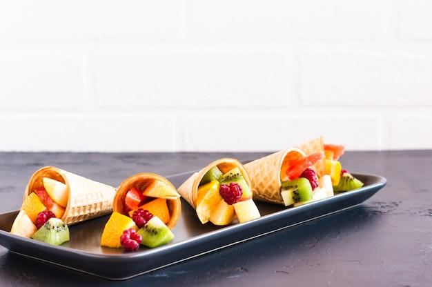 Corte as frutas maduras em cones de waffle em azul. em uma mesa preta contra uma parede de tijolos brancos.