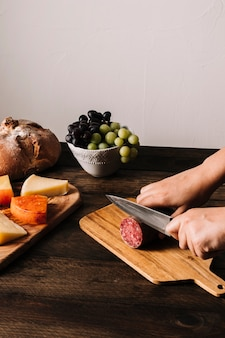 Corte as mãos cortando salsicha defumada