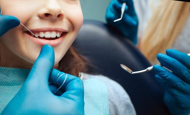 Corte as mãos em luvas de látex para usar fio dental nos dentes da frente da criança. mulher segura ferramentas dentárias ao lado.