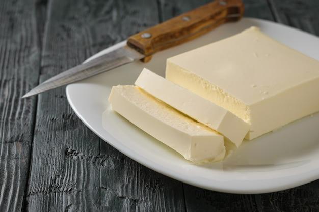 Corte com uma faca um pedaço de queijo sérvio sobre uma mesa de madeira. a vista do topo. produto lácteo. postura plana.