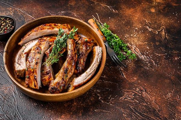 Corte costeletas de cordeiro grelhadas para churrasco em um prato de madeira.