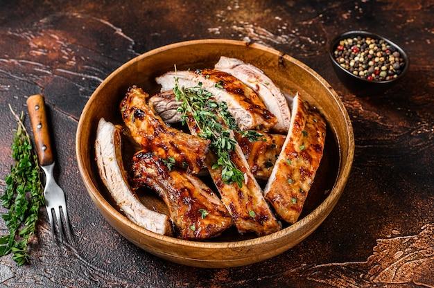 Corte costeletas de costela de cordeiro grelhadas para churrasco em um prato de madeira. fundo escuro. vista do topo.