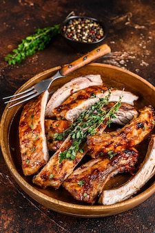 Corte costeletas de porco grelhadas para churrasco em um prato de madeira. fundo escuro. vista do topo.