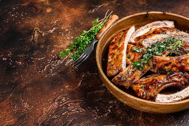 Corte costeletas de porco grelhadas para churrasco em um prato de madeira. fundo escuro.