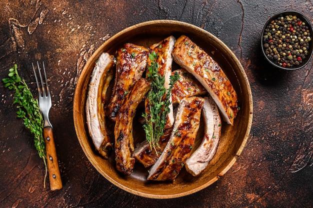 Corte costeletas de porco grelhadas para churrasco em um prato de madeira.