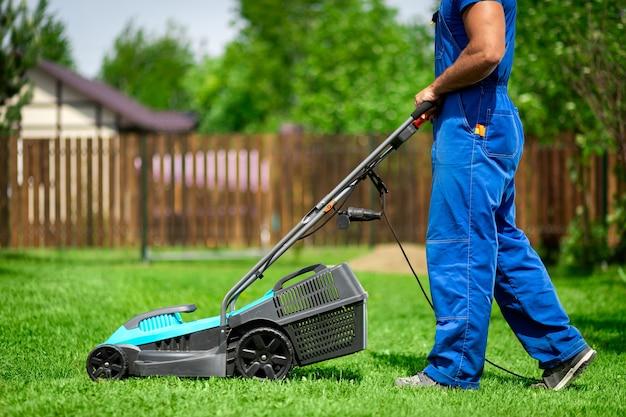Corte da grama do gramado. trabalhador cortando grama em um jardim verde