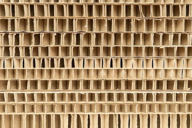 Corte da pilha de papelão de favo de mel com grandes células como plano de fundo