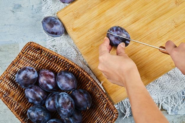 Corte de ameixa fresca na placa de madeira com cesto de ameixas.