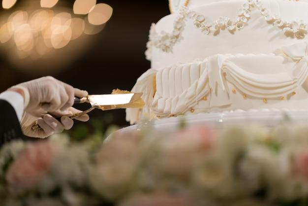 Corte de bolo de casamento, casal de mãos dadas, celebração